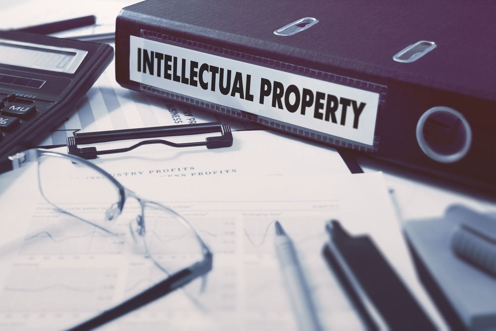 Office folder with inscription Intellectual Property on Office Desktop with Office Supplies. Business Concept on Blured Background. Toned Image.